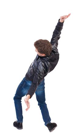 hombre cayendo: Equilibrio joven o esquivar la caída del hombre. Vista posterior recogida de las personas. backside vista de la persona. Aislado sobre fondo blanco. El chico de la chaqueta de cuero cae de espaldas. Foto de archivo