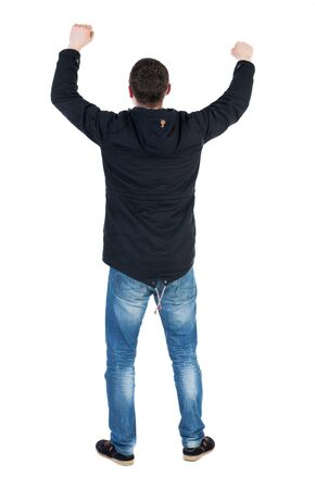 Back view of  man.  Raised his fist up in victory sign.   Rear view people collection.  backside view of person.  Isolated over white background. A guy in a black jacket with a hood over his head with his fists waving photo