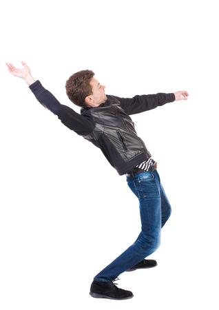 equilibrio: Equilibrio joven o esquivar la caída del hombre. Vista posterior recogida de las personas. backside vista de la persona. Aislado sobre fondo blanco. El hombre sopla el viento. El chico de la chaqueta de cuero cae de espaldas. vista lateral.