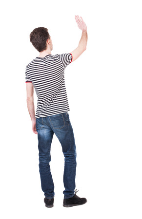 man rear view: Back view of handsome man greeting waving from his hands. Standing young guy in jeans. Rear view people collection.  backside view of person.  Isolated over white background. Curly French waves.