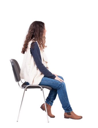 1 person: back view of young beautiful  woman sitting on chair.  girl  watching. Rear view people collection.  backside view of person.  Isolated over white background. A girl in a white tank top sitting on a stool and looking to the right.