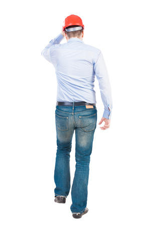 observes: Back view of walking engineer in helmet.  Rear view people collection. Backside view of person. Isolated over white background.  Engineer holding a hard hat goes forward.