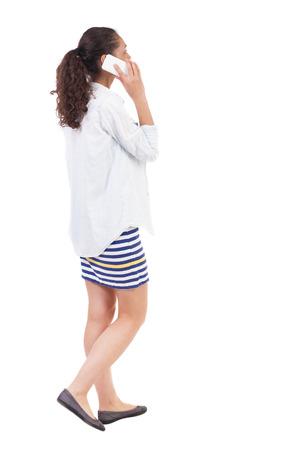 personas caminando: una vista lateral de una mujer caminando con un tel�fono m�vil. hermosa chica rizada en movimiento. backside vista de la persona. Vista posterior recogida de las personas. Aislado sobre fondo blanco. Mujer afro afroamericana en movimiento con entusiasmo hablar por tel�fono