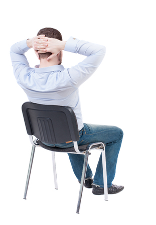 hands behind head: back view of business man sitting on chair.  businessman watching. Rear view people collection.  backside view of person.  Isolated over white background. The guy in the blue shirt sitting in a chair with his hands behind his head.