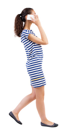 sexy pictures: a side view of a woman walking with a mobile phone. beautiful curly girl in motion.  backside view of person.  Rear view people collection. Isolated over white background.  African-American woman in a striped dress on the move enthusiastically talking on