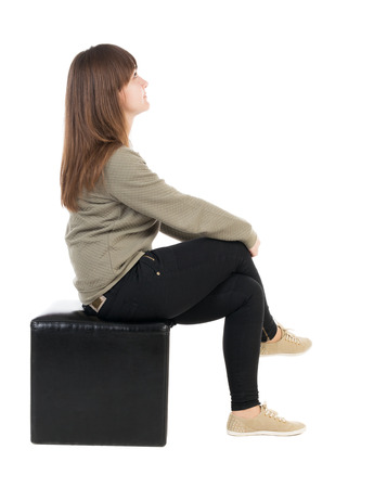 back view of young beautiful  woman sitting.  girl  watching. Rear view people collection.  backside view of person.  Isolated over white background. Pretty teenage girl sitting on a black ottoman legs crossed.