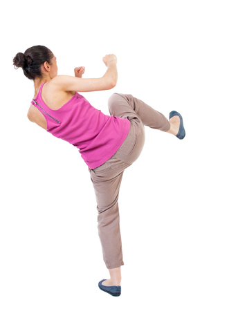 wimp: skinny woman funny fights waving his arms and legs. Rear view people collection.  backside view of person.  Isolated over white background. African-American woman kick foot. Stock Photo