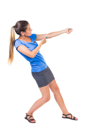 woman rope: back view of standing girl pulling a rope from the top or cling to something. girl  watching. Rear view people collection.  backside view of person.  Isolated over white background. Girl in a gray skirt and blue shirt pulling the rope something heavy righ