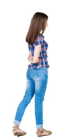 his shirt sleeves: back view of standing young beautiful  woman.  girl  watching. Rear view people collection.  backside view of person.  Isolated over white background. Girl in a blue plaid shirt with short sleeves is hands clasped behind his back. Stock Photo