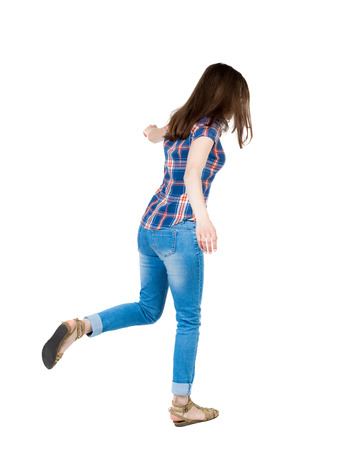 balances: Back view woman Balances waving his arms.   Standing young girl in jeans. Rear view people collection.  backside view of person.  Isolated over white background. A young girl in a checkered blue with red stripes on the right foot jumps.