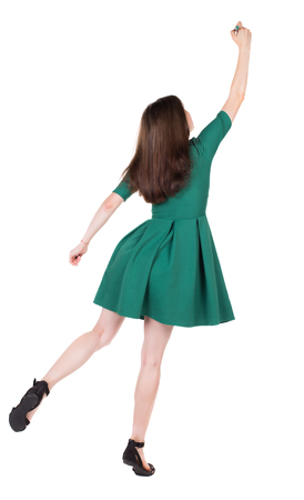 tiptoes: back view of writing beautiful woman. Young girl in dress. Rear view people collection.  backside view of person. Isolated over white background. The girl in stylish green dress standing on tiptoes writes a felt-tip pen on top.