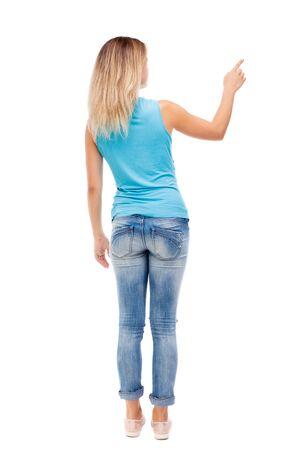 dedo señalando: Vista posterior de señalar de la mujer. hermosa chica. Vista posterior recogida de las personas. trasero vista de la persona. Aislado sobre fondo blanco. La muchacha en pantalones vaqueros y una camisa azul muestra un dedo de su mano derecha.