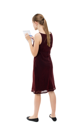 girl in burgundy dress: back view of  stands woman takes notes in a notebook. girl  watching. Rear view people collection.  backside view of person.  Isolated over white background. A girl in a burgundy dress writes in a notebook. Stock Photo
