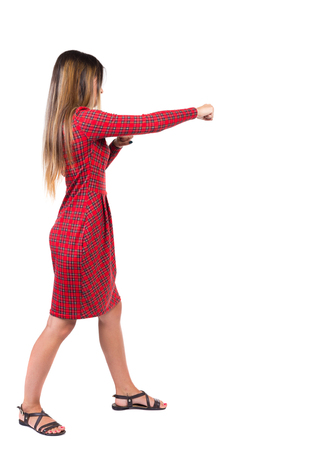 wimp: skinny woman funny fights waving his arms and legs. Isolated over white background. Long-haired girl in a red plaid dress hits right hand.