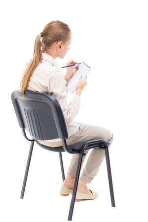back view of young beautiful  woman sitting on chair and  takes notes in a notebook.  girl  watching. Rear view people collection.  backside view of person.  Isolated over white background. A girl sits in a light denim suit and writes.