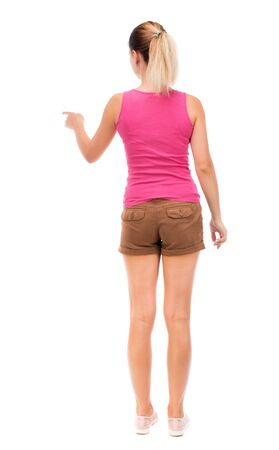 woman hands up: back view of young woman presses down on something. Isolated over white background. Rear view people collection. backside view of person. The girl in brown shorts and a pink tank top is pointing to the left.