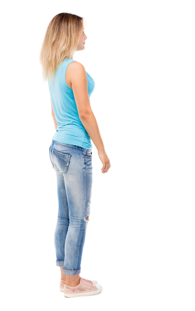 back view of standing young beautiful  woman.  girl  watching. Rear view people collection.  backside view of person.  Isolated over white background. The girl in jeans and a blue t-shirt standing sideways. Stock Photo