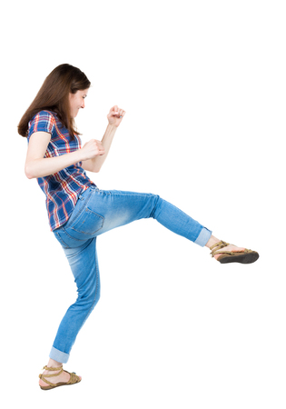 wimp: skinny woman funny fights waving his arms and legs. Isolated over white background. A young girl in a checkered blue with red stripes hit the right foot.