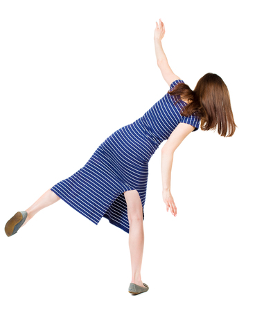 balances: Back view woman Balances waving his arms.   Standing young girl in dress. Rear view people collection.  backside view of person.  Isolated over white background. Girl in a blue striped dress trying to stay on the right foot.