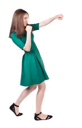 skinny woman: skinny woman funny fights waving his arms and legs. Isolated over white background. A girl in a long green dress boxing.