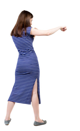 skinny woman: skinny woman funny fights waving his arms and legs. Rear view people collection.  backside view of person.  Isolated over white background. A girl in a long blue dress boxing.