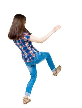 balances: Back view woman Balances waving his arms.   Standing young girl in jeans. Rear view people collection.  backside view of person.  Isolated over white background. A young girl in a checkered blue with red stripes on the back of falling
