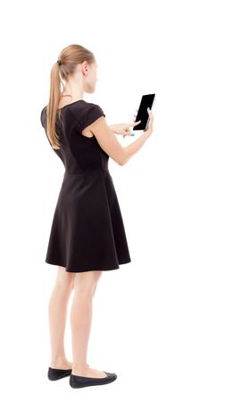 back view of standing young beautiful  girl with tablet computer in the hands of. girl  watching. Rear view people collection.  backside view of person.  Isolated over white background. The blonde in a black short dress working on the tablet. Stock Photo