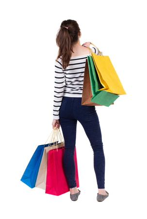 frenchwoman: back view of going  woman woman with shopping bags. beautiful brunette girl in motion.  backside view of person.  Rear view people collection. Isolated over white background. Frenchwoman in vest standing with lots of shopping bags. Stock Photo