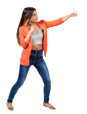 wimp: skinny woman funny fights waving his arms and legs. Isolated over white background. The girl in the red jacket standing in a boxing pose and hit his left hand. Stock Photo