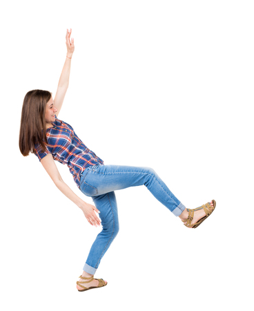 stumble: Balancing young woman.  or dodge falling woman. Rear view people collection.  backside view of person.  Isolated over white background. A young girl in a checkered blue with red stripes smiling teetering on the left leg. Stock Photo