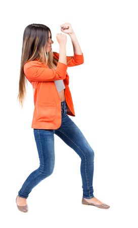 wimp: skinny woman funny fights waving his arms and legs. Isolated over white background. The girl in the red jacket standing in a boxing pose protecting her face from the blow.