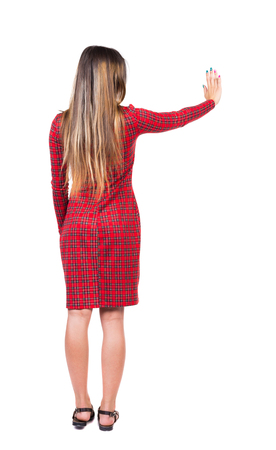 push people: back view of young woman presses down on something. Isolated over white background. Rear view people collection. backside view of person. Long-haired girl in a red plaid dress presses a button with your right hand.