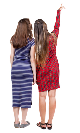 rear view girl: Back view of two pointing young girl. Rear view people collection.  backside view of person. beautiful woman friends  showing gesture. Rear view. Isolated over white background. Two girls in dresses show the mark. Stock Photo