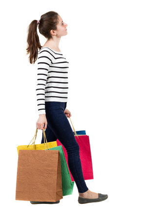 frenchwoman: back view of going  woman  with shopping bags . beautiful girl in motion.  backside view of person.  Rear view people collection. Isolated over white background. Frenchwoman in the vest goes right with shopping bags and looking upward.