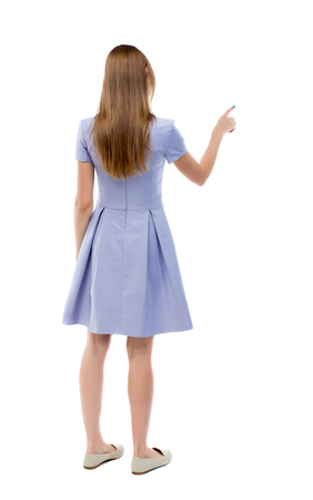 back view of young woman presses down on something. Isolated over white background. Rear view people collection. backside view of person. The girl in a blue dress and presses the button.