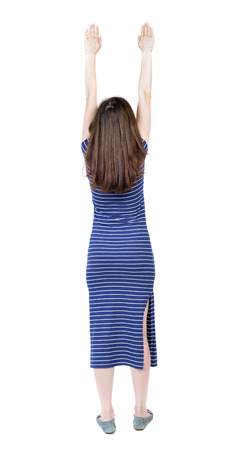 superman: Back view of  woman.  Raised his fist up in victory sign.  Rear view people collection.  backside view of person.  Isolated over white background. Girl in a blue striped dress flying in Superman pose. Stock Photo