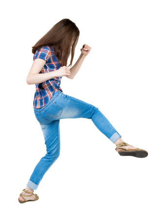 skinny woman: skinny woman funny fights waving his arms and legs. Isolated over white background. A young girl in a checkered blue with red stripes make kick-boxing punch.