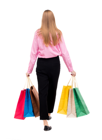 back view of going  woman  with shopping bags . beautiful girl in motion.  backside view of person.  Rear view people collection. Isolated over white background. Woman businessman went off with bags.