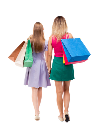go ahead: back view of  two walking women  with shopping bags. backside view of person.  Rear view people collection. Isolated over white background. Two pretty girls in fancy dresses go ahead with shopping bags thrown over his shoulders. Stock Photo