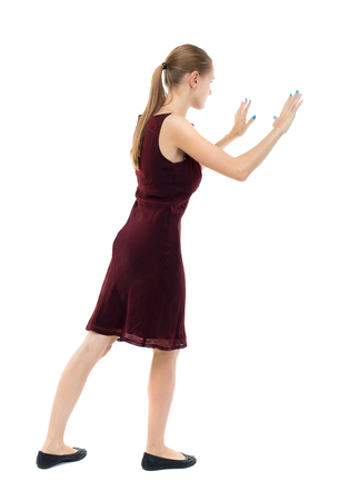 girl in burgundy dress: back view of woman pushes wall. Isolated over white background. Rear view people collection. backside view of person. Blonde girl in a burgundy dress leaned on something.