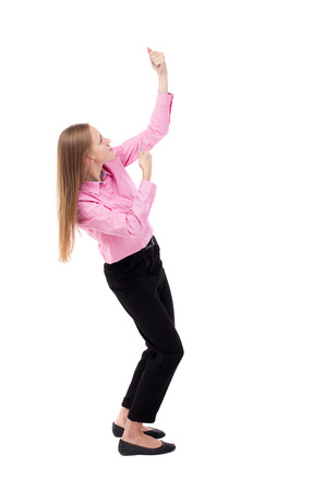 slacks: back view of standing business woman pulling a rope from the top or cling to something. girl  watching. Rear view people collection.  backside view of person.  Isolated over white background. The girl office worker in black slacks standing sideways pulls