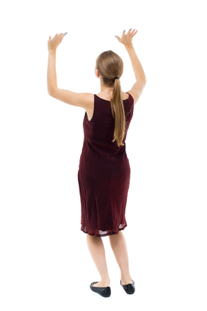 girl in burgundy dress: back view of woman  protects hands from what is falling from above. woMan holding a heavy load Rear view people collection.  backside view of person.  Isolated over white background. Blonde girl in a burgundy dress holding something over him. Stock Photo