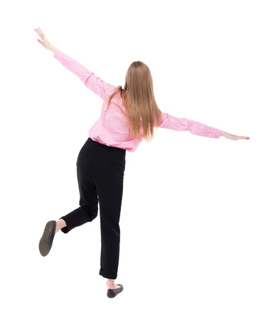 balances: Balancing young business woman.  or dodge falling woman. Rear view people collection.  backside view of person.  Isolated over white background. The girl office worker in black pants balances on the right foot. Stock Photo