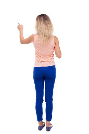 mujeres de espalda: Vista posterior de señalar de la mujer. hermosa chica. Vista posterior recogida de las personas. trasero vista de la persona. Aislado sobre fondo blanco. rubia en pantalones azules está señalando con su mano izquierda.