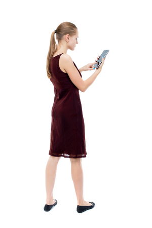girl in burgundy dress: back view of standing young beautiful  girl with tablet computer in the hands of. girl  watching. Rear view people collection.  backside view of person.  Isolated over white background. The blonde burgundy dress standing upright holding hands Tablet PC.