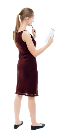 girl in burgundy dress: back view of  stands woman takes notes in a notebook. girl  watching. Rear view people collection.  backside view of person.  Isolated over white background. Blonde girl in a burgundy dress thoughtfully looks in a notebook. Stock Photo