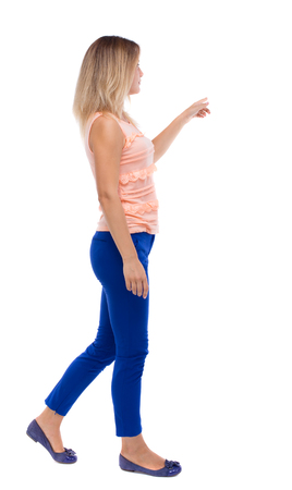 looking back: back view of pointing walking  woman. going girl pointing.  backside view of person.  Rear view people collection. Isolated over white background. blonde in blue pants is holding up his left hand to the right.