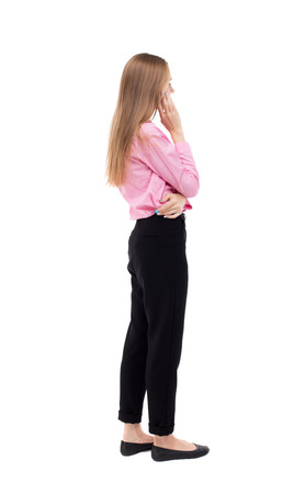 woman think: back view of standing young beautiful  woman.  girl  watching. Rear view people collection.  backside view of person.  The girl office worker in black trousers stands sideways and looks thoughtfully left.