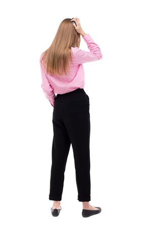 rear view girl: Back view of shocked woman. upset young girl. Rear view people collection.  backside view of person.  Isolated over white background. The girl office worker in black pants is holding his head thoughtfully.