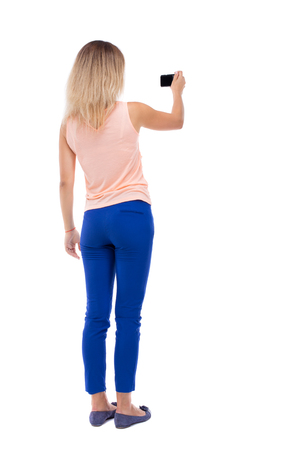 mujeres de espalda: Vista posterior del pie hermosa mujer joven y el uso de un teléfono móvil. niña viendo. Vista posterior recogida de las personas. trasero vista de la persona. Aislado sobre fondo blanco. Rubia en pantalón azul hace que el vídeo se sujeta la cámara con una mano. Foto de archivo